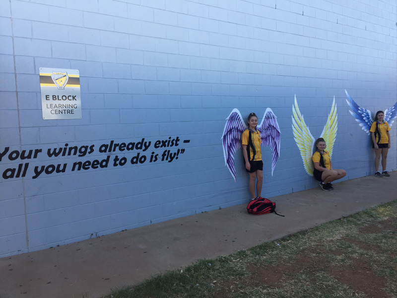 Students leaning against an artwork mural